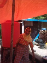 Bright orange water tank Image via Oxfam